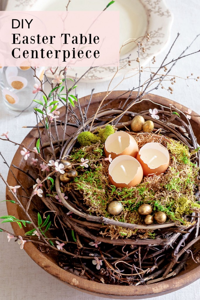 Close up of an Easter table centerpiece in a round wooden dough ball with grapevines, branches, moss and eggshell candles.