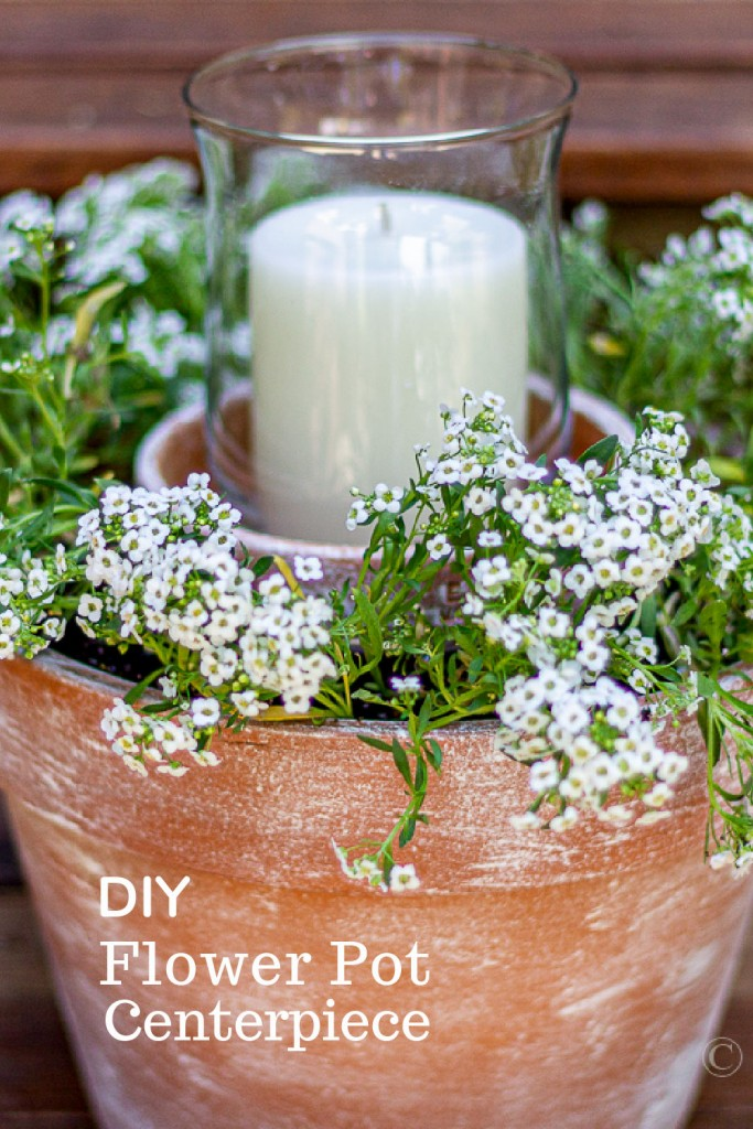 Potted clay plant centerpiece with a candle and white alyssum flowers.