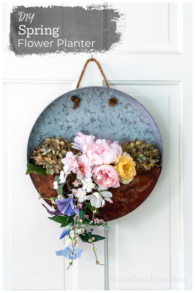 Galvanized hanging planter with faux spring flowers on a white door.