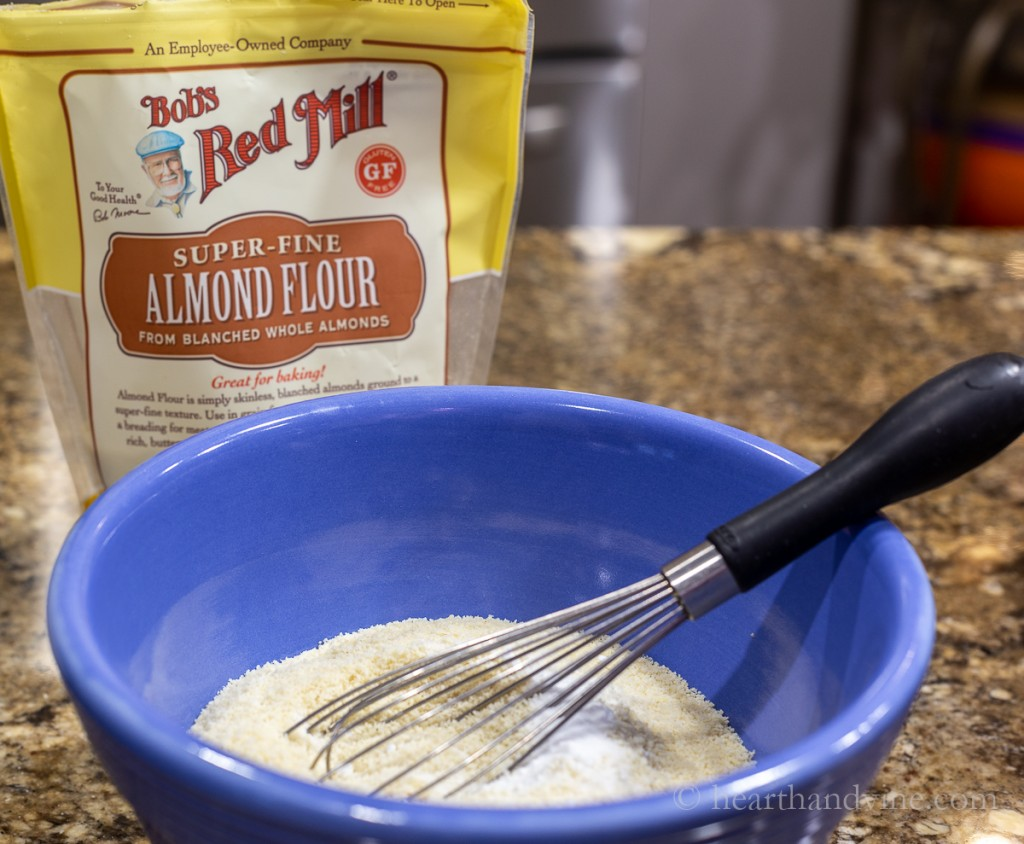 Blue mixing bowl with almond flour, baking soda and salt with a wire whisk.