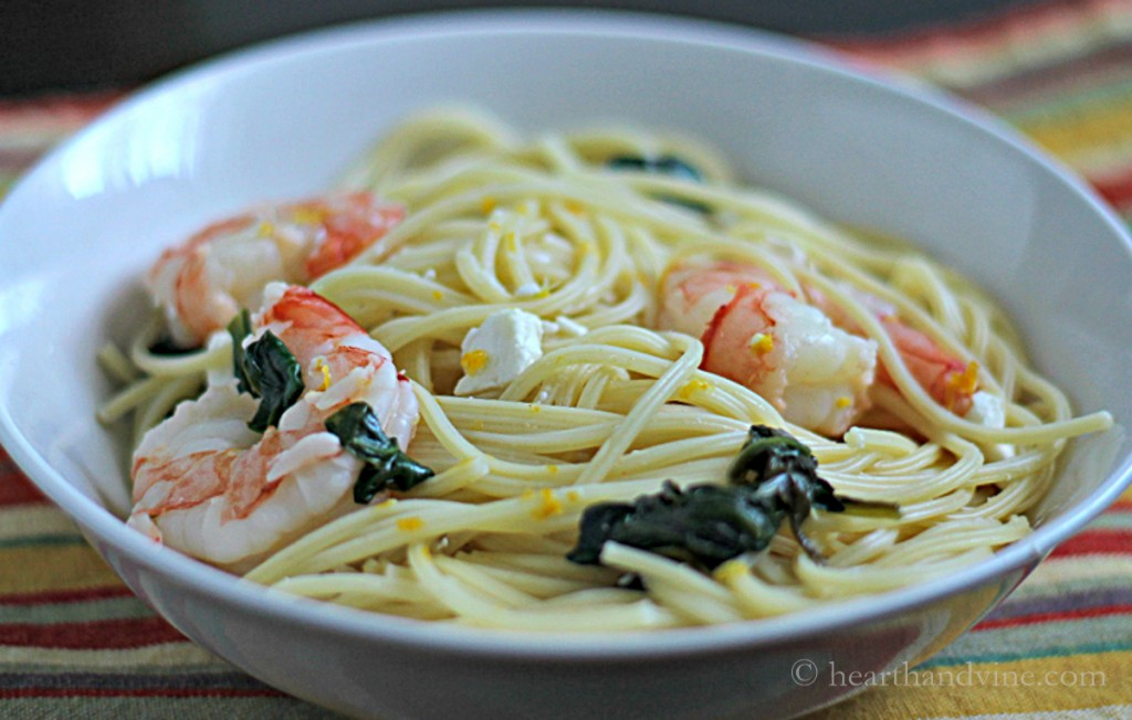 Bowl of pasta with shrimp, feta and spinach.