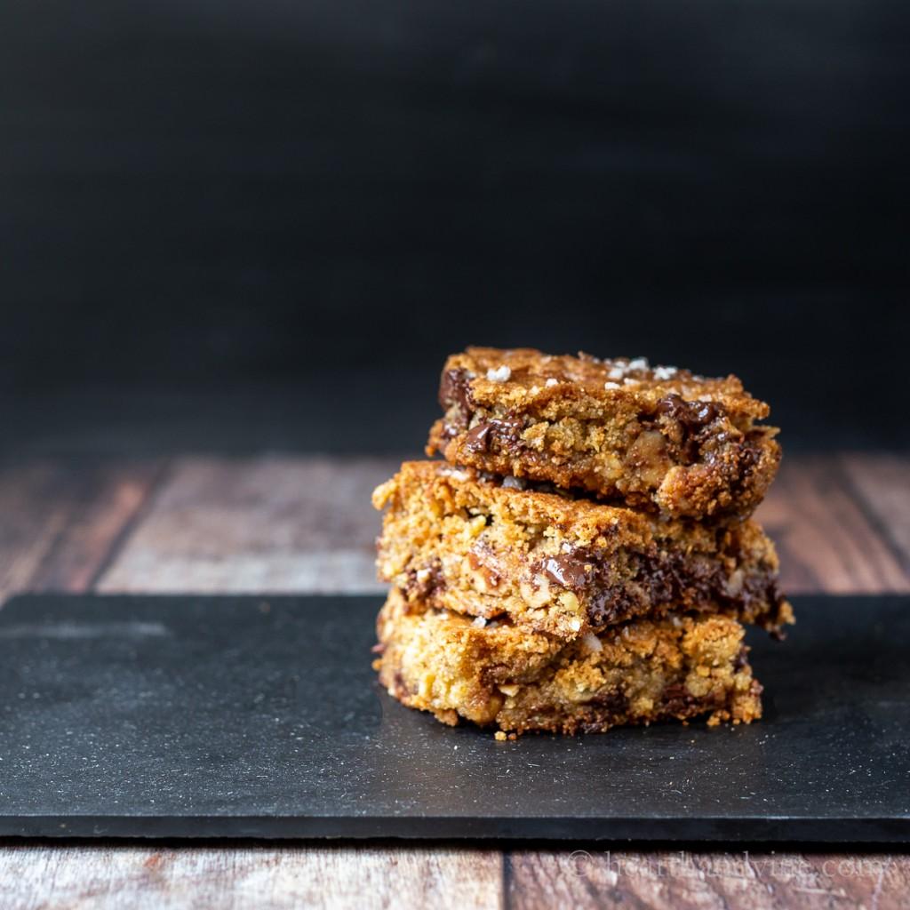 Healthy oatmeal chocolate chunk bars stacked on a black slate.