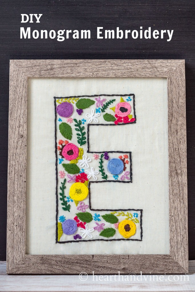 Floral embroidered monogrammed E pattern on muslin in a wood frame.