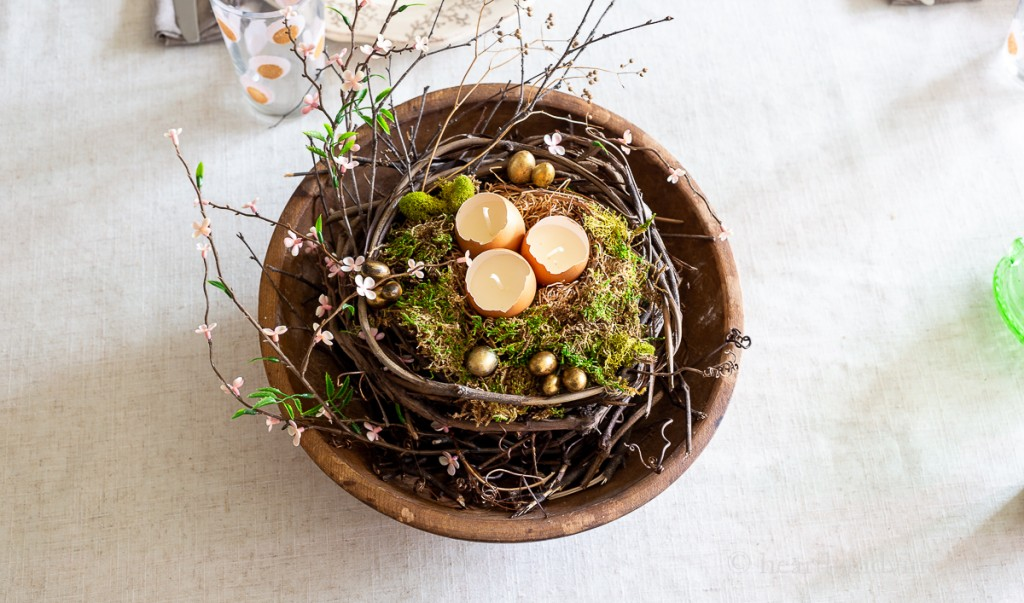 Easter table centerpiece made from a round dough bowl and natural elements like grapevines, moss and eggshell candles.