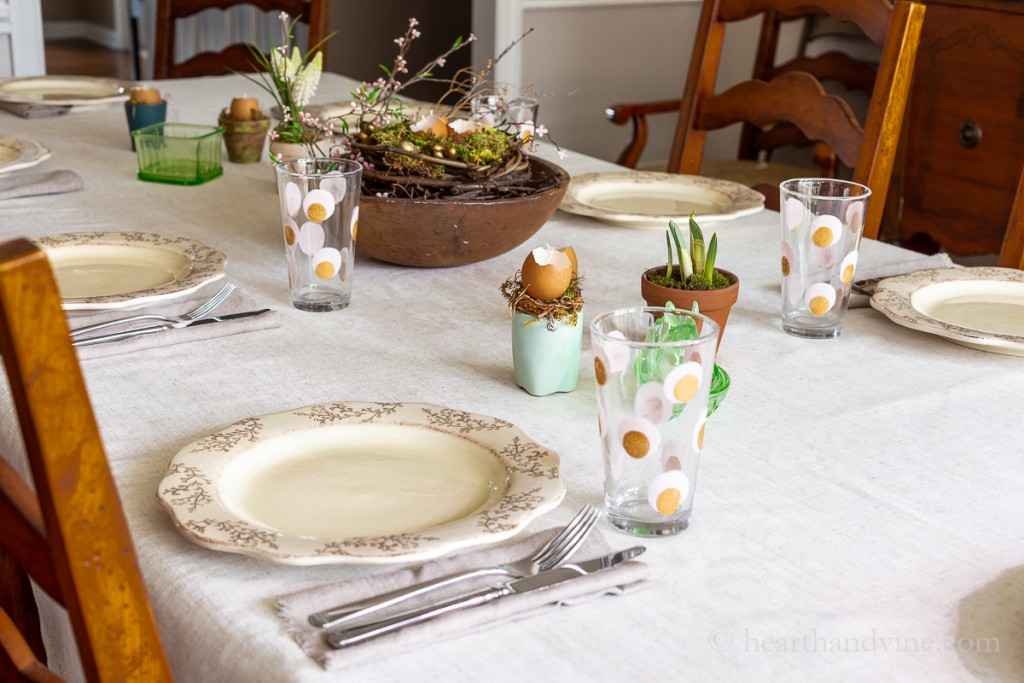 Table set for Easter with natural spring elements like spring bulbs, eggshell candles and a wooden centerpiece with a nest and blossoms.