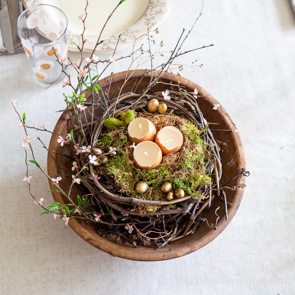 Large wood bowl with grapevines, moss mini gold eggs, eggshell candles and faux pink blossoms.