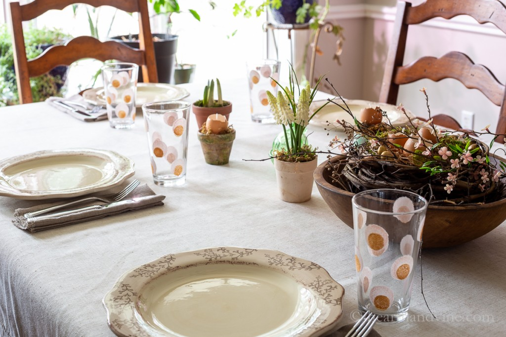Spring table decorations with pink and gold painted water glasses, eggshell candles in pots on the table and in a nest in the centerpiece with moss and pink blossoms.