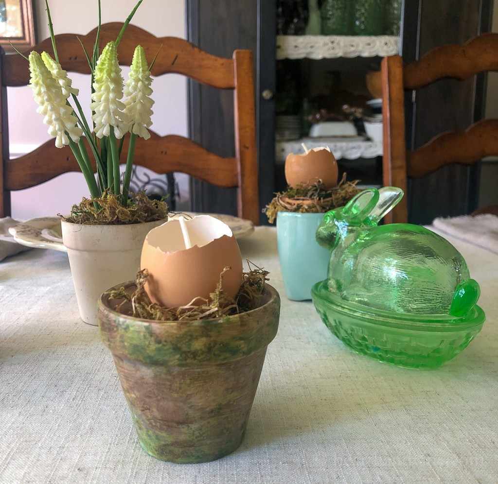 Table with colored clay pot holding an eggshell candle next to a glass bunny candy holder and other pots in the background.