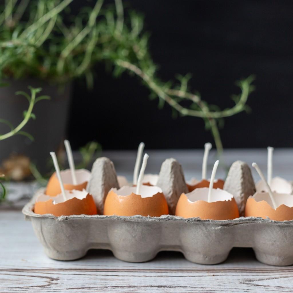 Homemade candles using eggshells in a cardboard carton.