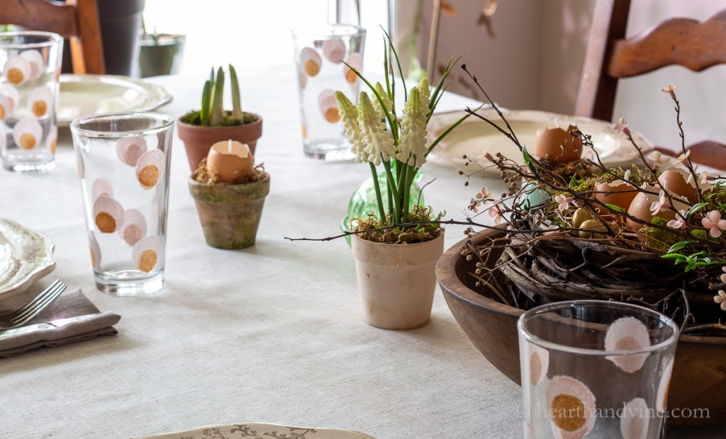 Easter table decorated with spring blooms, and pots with eggshell candles.