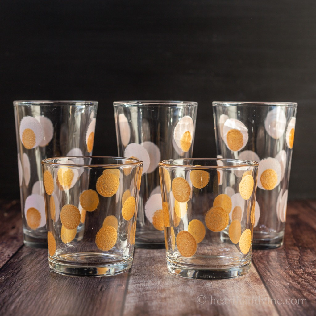 Short old fashioned glasses with gold dots in front of tall water glasses with pink and gold dots.