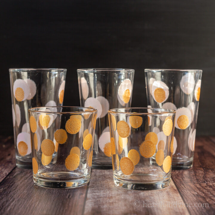 Tall and short glasses painted with gold and pink dots.