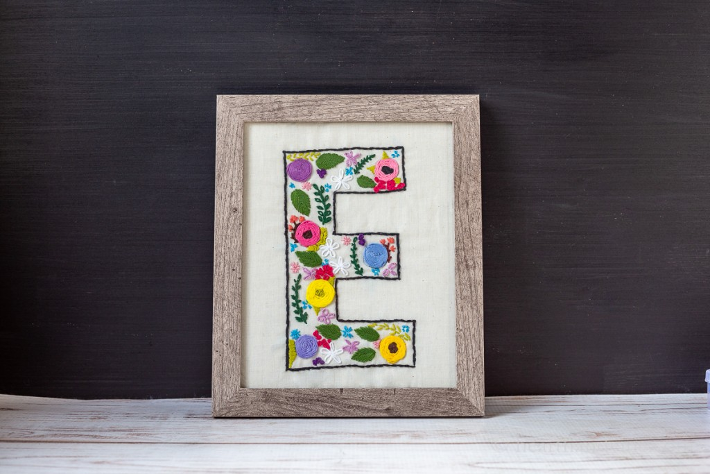 Floral embroidered pattern on muslin in the shape of a monogrammed E placed in a wood frame.