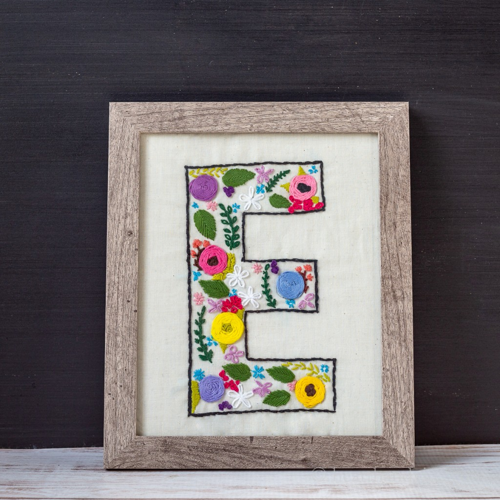 Embroidered monogram letter in a floral design and placed in a wood frame