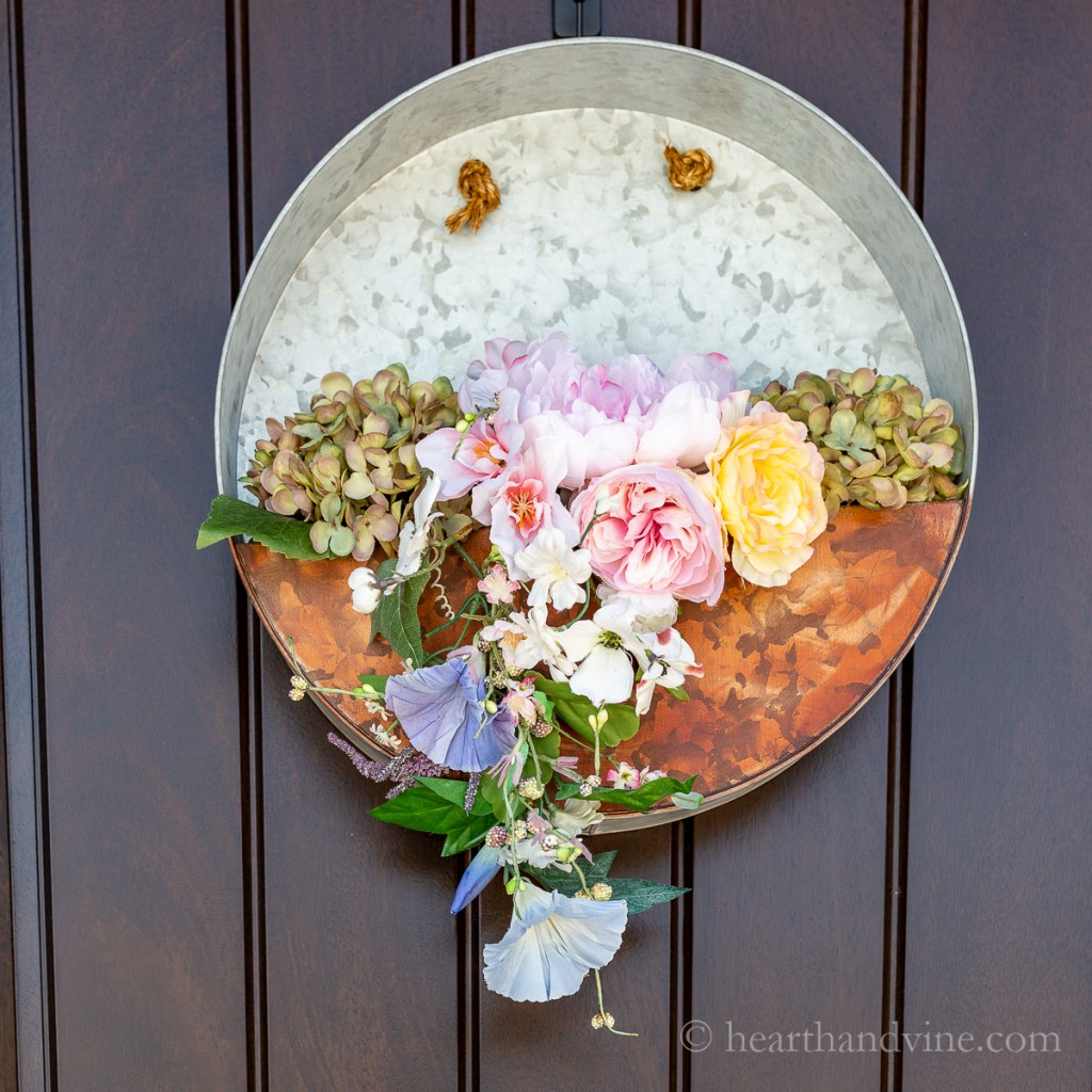 Artificial spring flowers in a round galvanized metal hanging planter on a brown door.