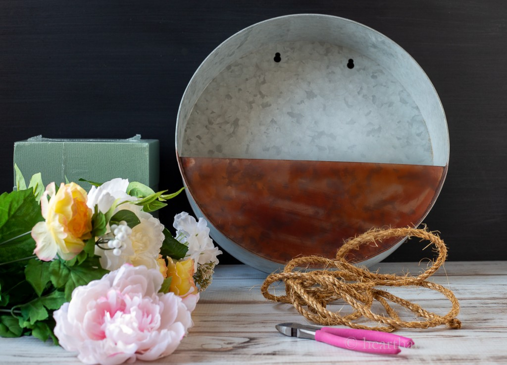 Supplies including a galvanized metal planter, faux flowers, floral foam, sisal rope and metal cutter.