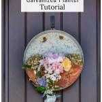 Metal planter with flowers on a brown door.