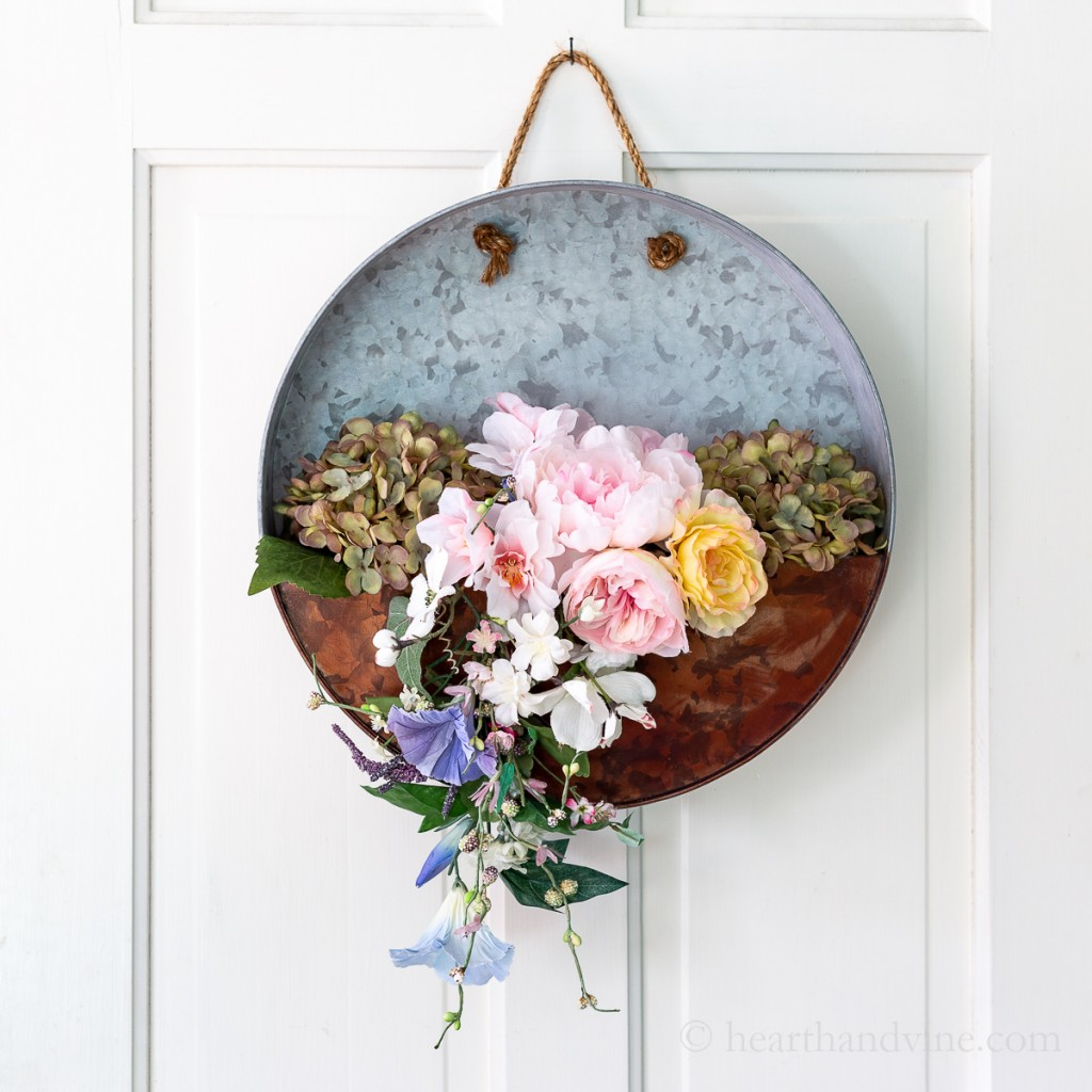 A white door with a metal wreath full of spring flowers hanging with rope.