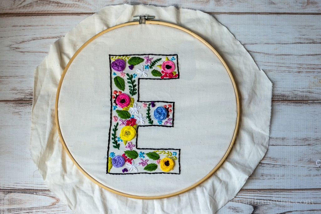 Completed floral embroidery stitches on muslin in the shape of an E with flowers and leaves.