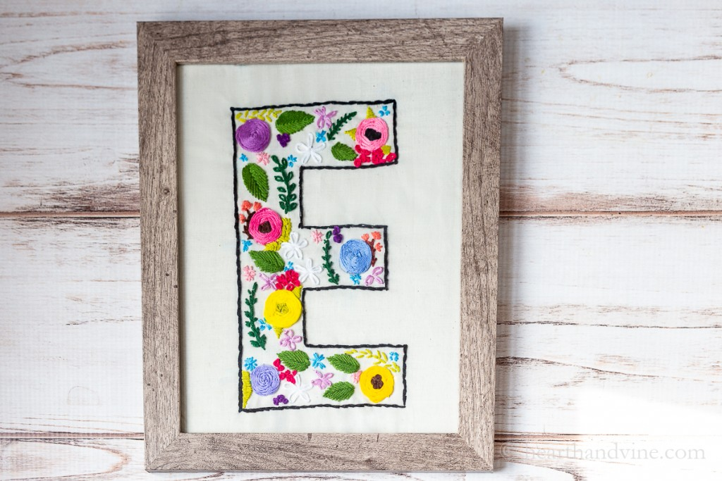Floral embroidered pattern on a monogrammed E placed in a wood frame.