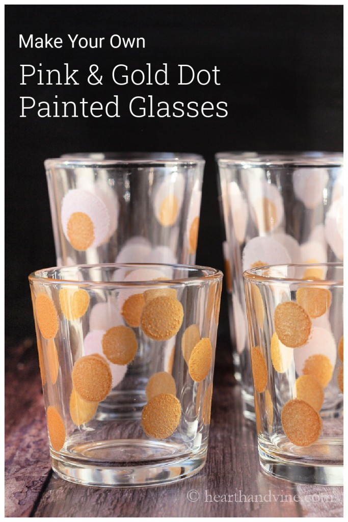 Short rocks glasses with gold dots in front of tall water glasses with pink and gold dots.