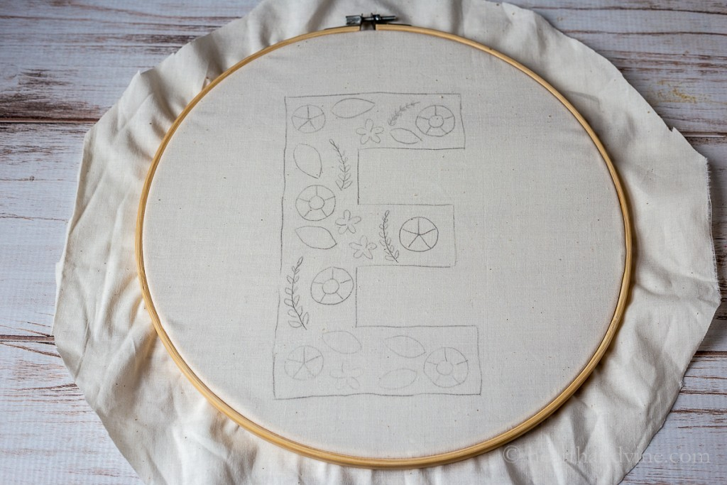 E monogram with embroidery shapes on muslin in a large embroidery hoop.