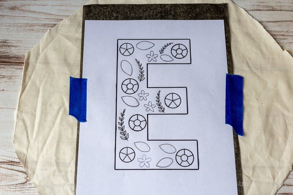 Graphic E on top of carbon paper on top of muslin taped down with blue painters tape.