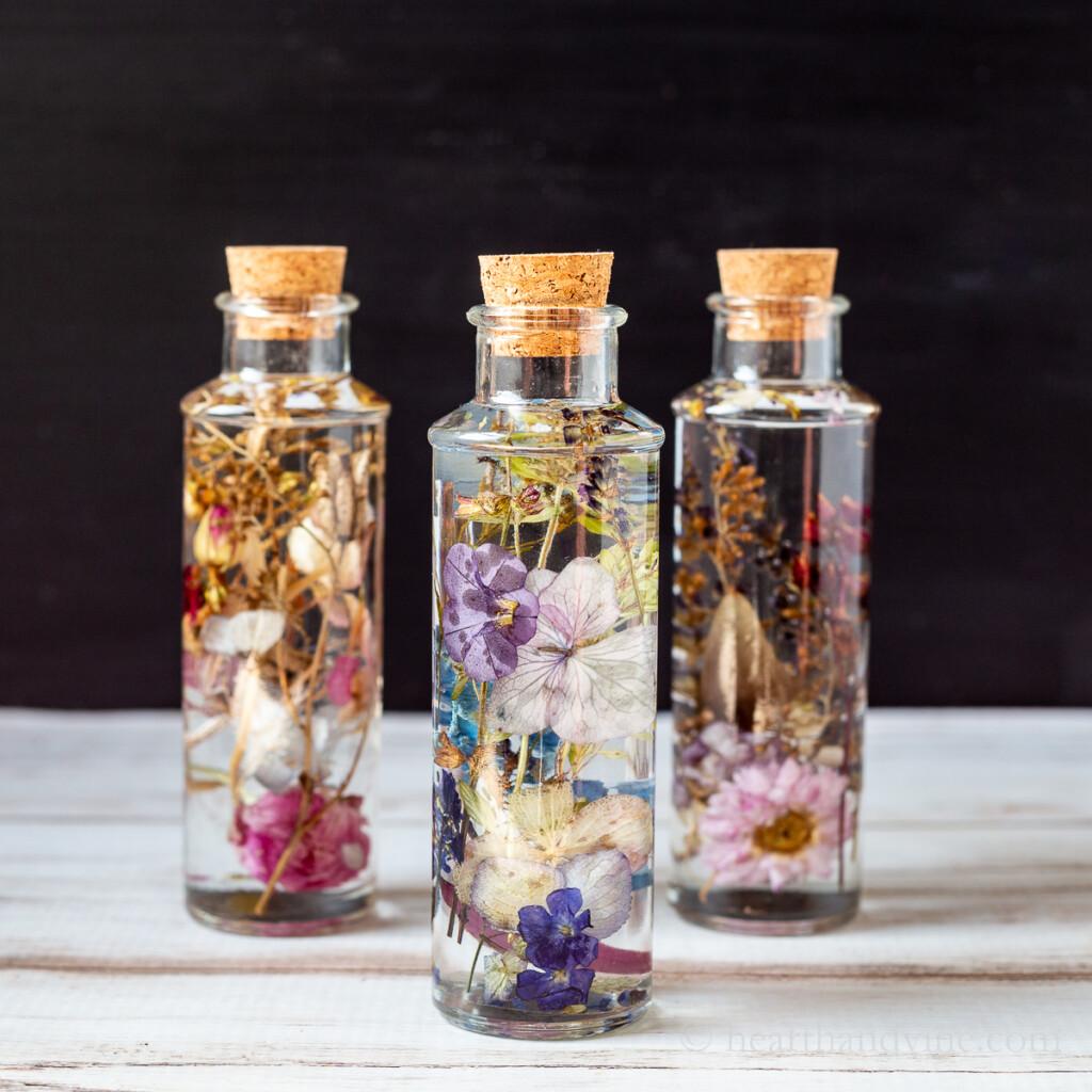 Three dried flowers in oil bottles.