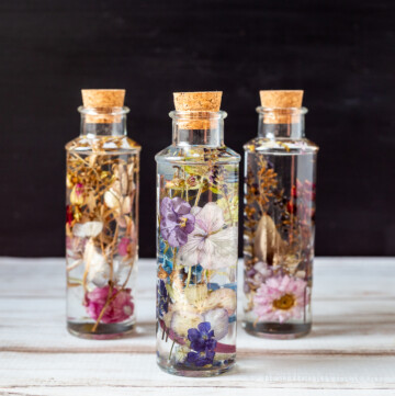 Three dried flowers in oil bottles