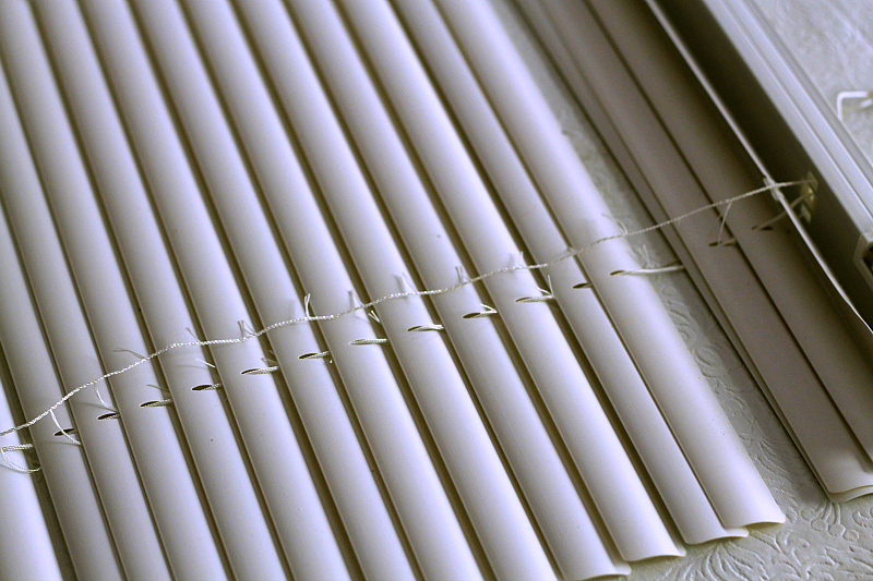 Close up image of cutting the cording on a mini blind
