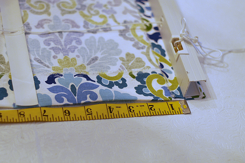 Fabric under top of the mini blind and a tape measurer on the side to determine spacing.