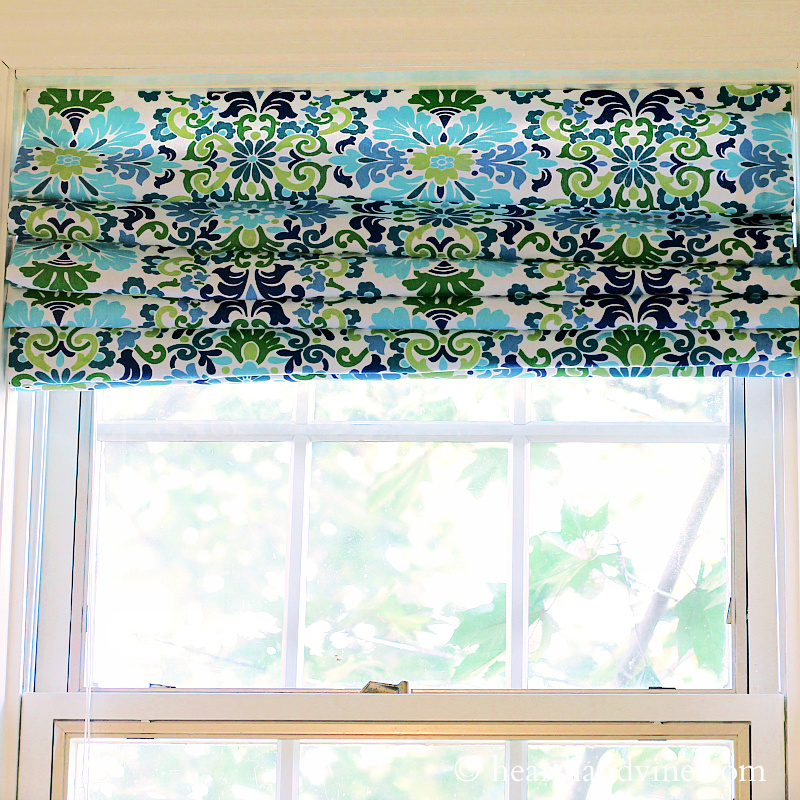 Blue and green Roman shades made from mini blinds hanging in a window.
