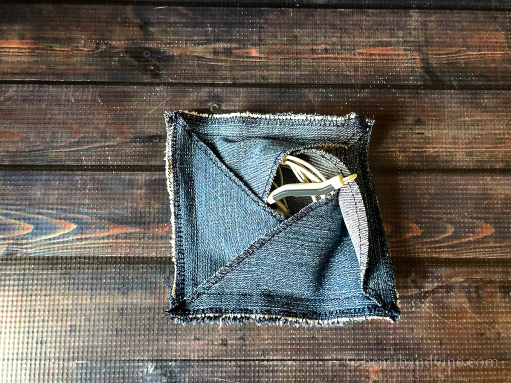 Square denim pouch with earbud piece sticking out.