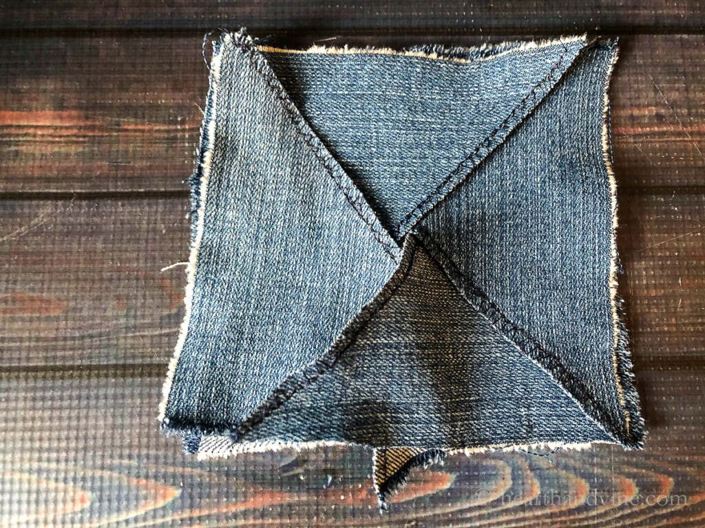 Four over-lapping denim triangles on top of a square piece of denim.