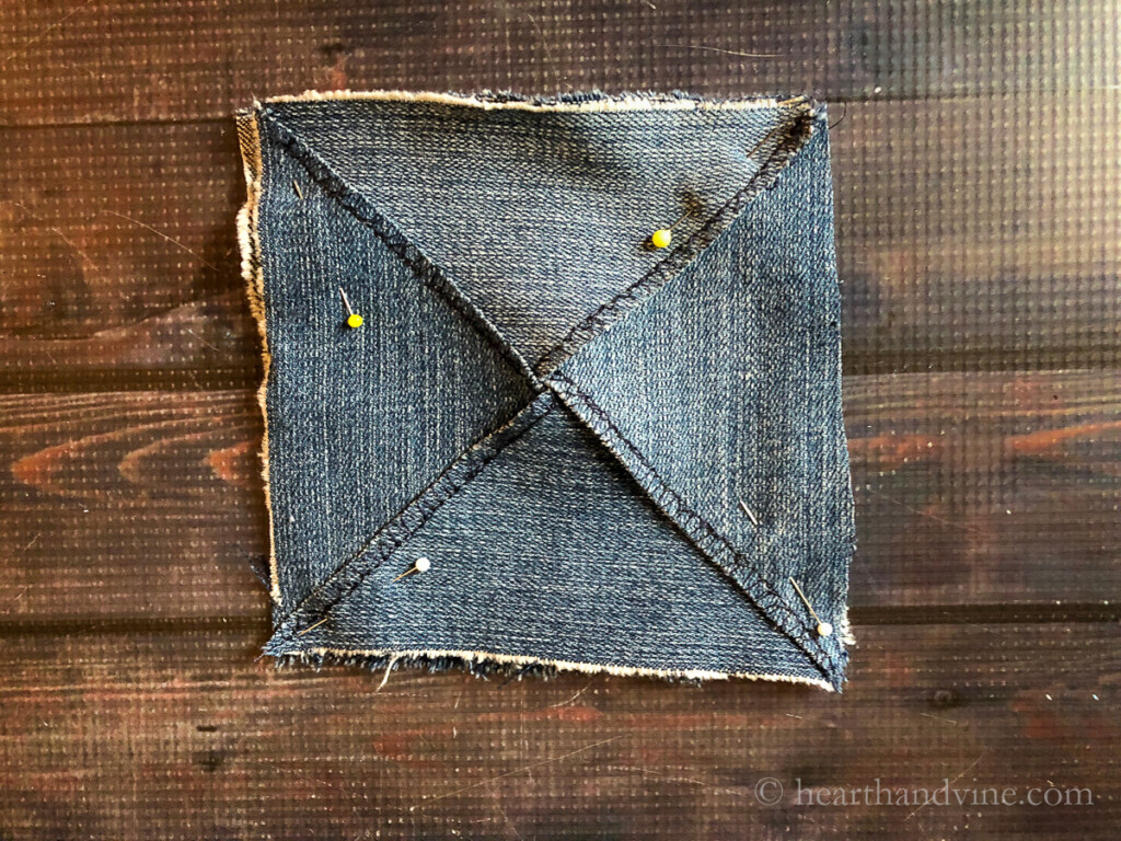 Denim pouch triangle shapes pinned to a square backing.