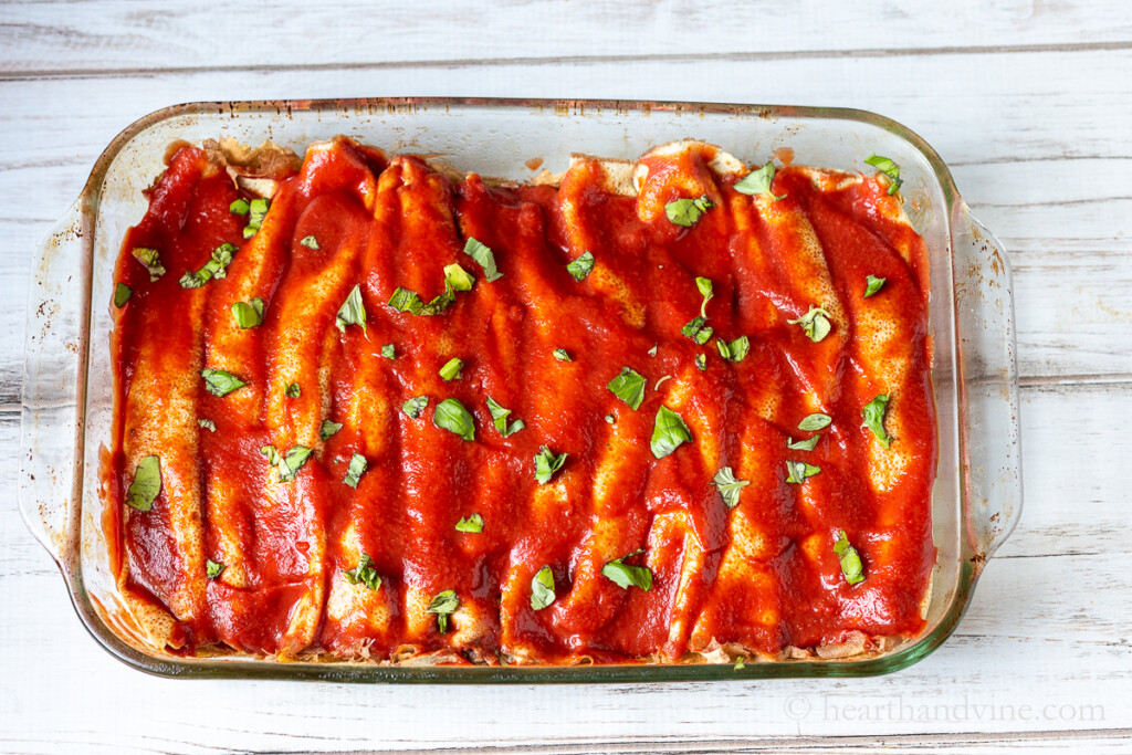 Casserole baking dish with Crepini filled cannelloni topped with tomato sauce and fresh basil.