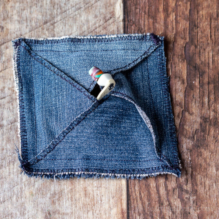 Denim pouch with earbuds inside