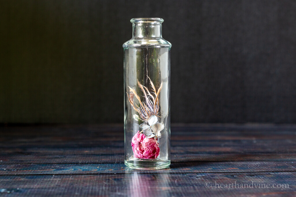 Glass bottle with a few dried flowers inside.