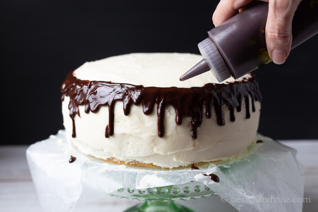 Chocolate drip ganache poured from a squeeze bottle on the edge of a two layer white cake.