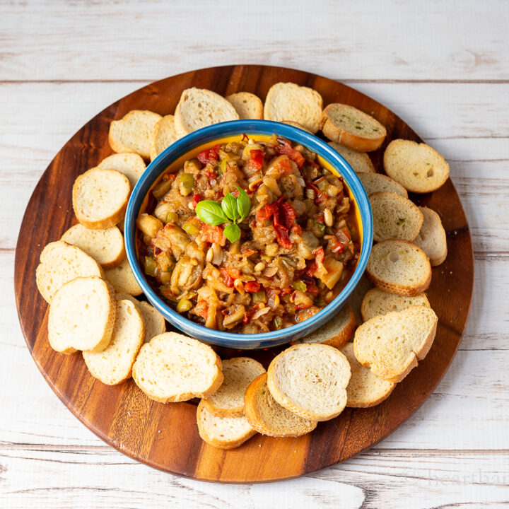 Roasted eggplant caponata on a plate with bread rounds