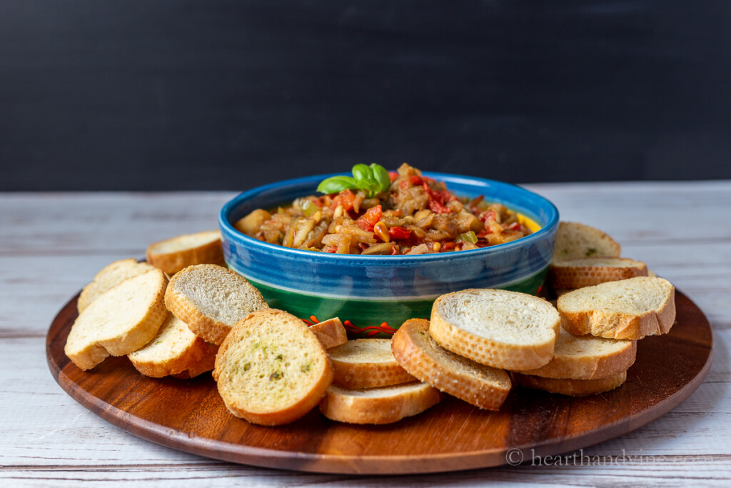 A bowl of eggplant caponata on a round wood board with slices bread rounds around the bowl.
