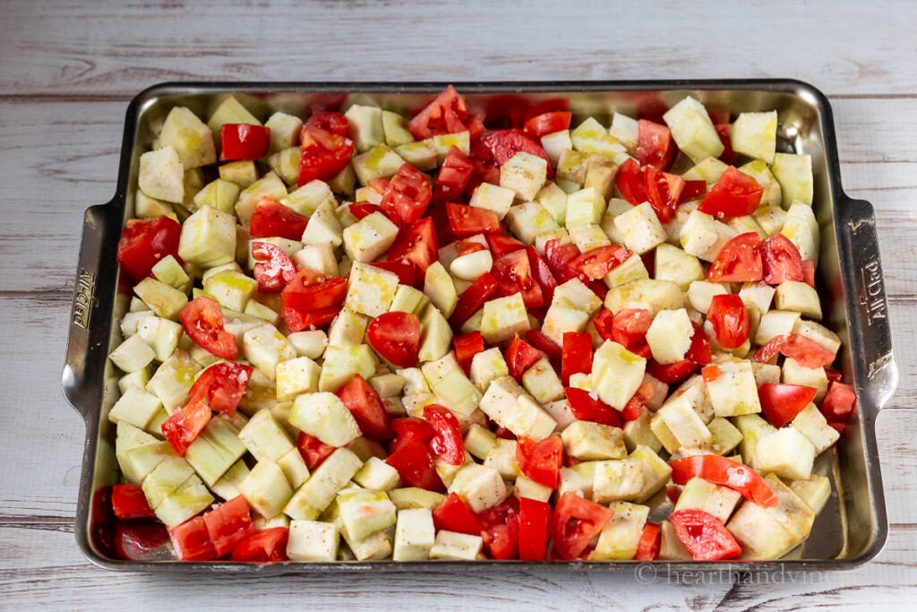 Cube eggplant, chopped tomatoes and a few garlic cloves on a large baking sheet pan.