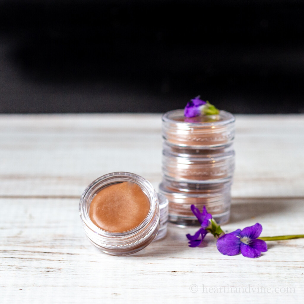 Violet lip balm in small round containers and a few live violet flowers