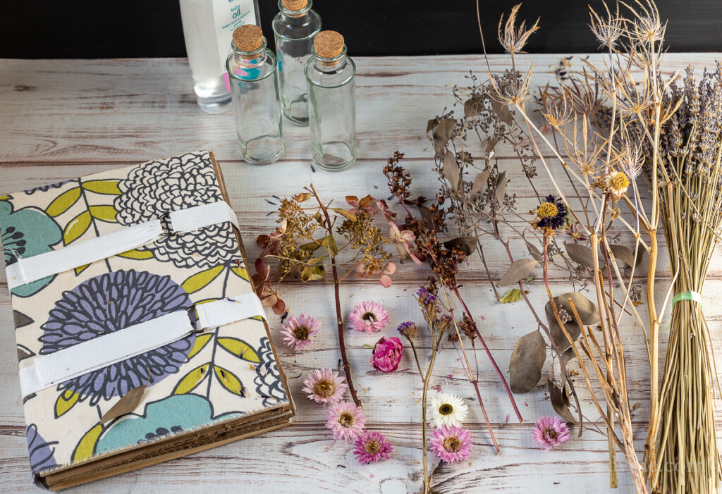 Flower press and dried flowers on table. Glass bottles with cork stoppers.