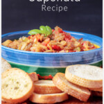 Bowl of roasted eggplant caponata on a plate with bread rounds