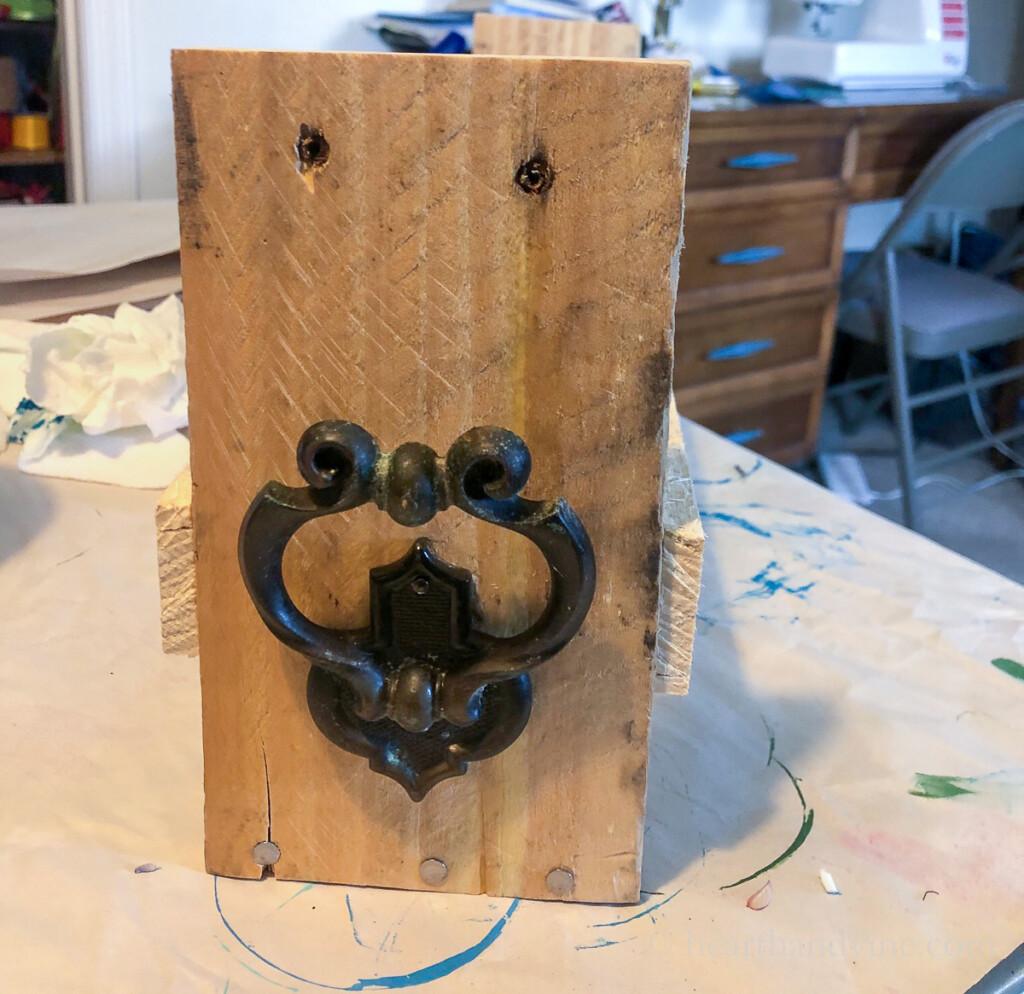 Old cabinet hardware on side of wood pallet.