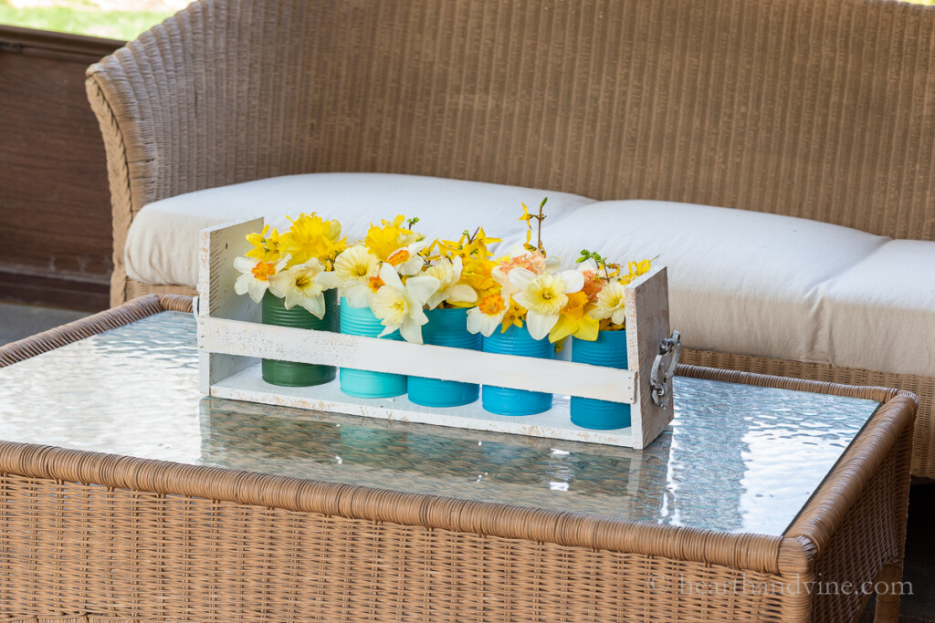 Tin cans in wood pallet caddy holding daffodils on a porch coffee table.