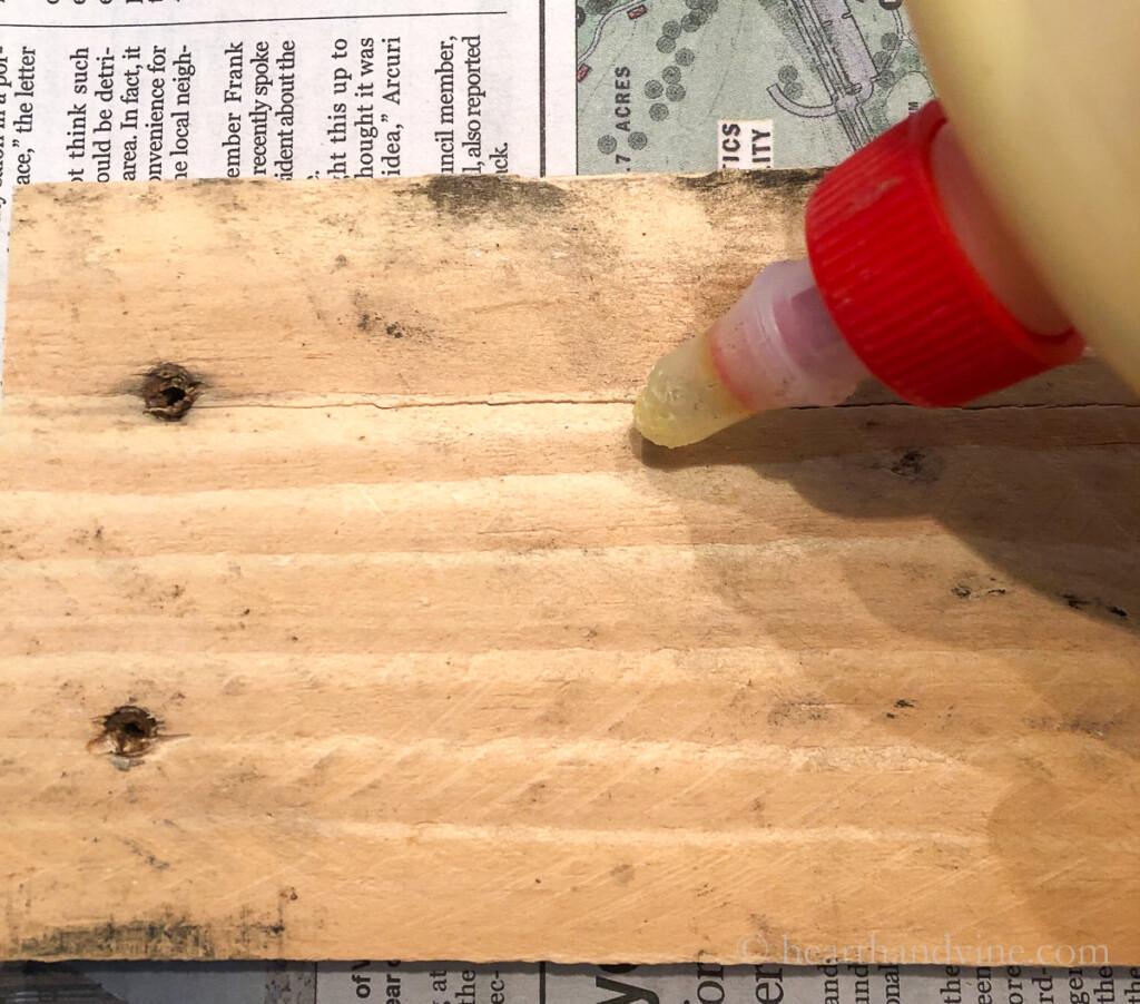 Wood glue  into cracks of pallet wood.