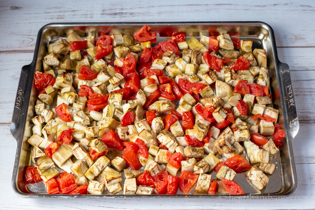 Roasted eggplant, chopped tomatoes and a few garlic cloves on a large baking pan.