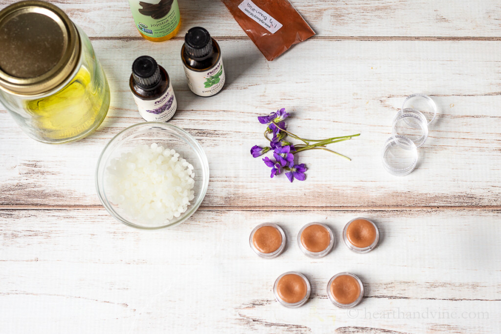Beeswax pellets, fresh violets, essential oils, mica powder and small containers filled with violet balm/salve.